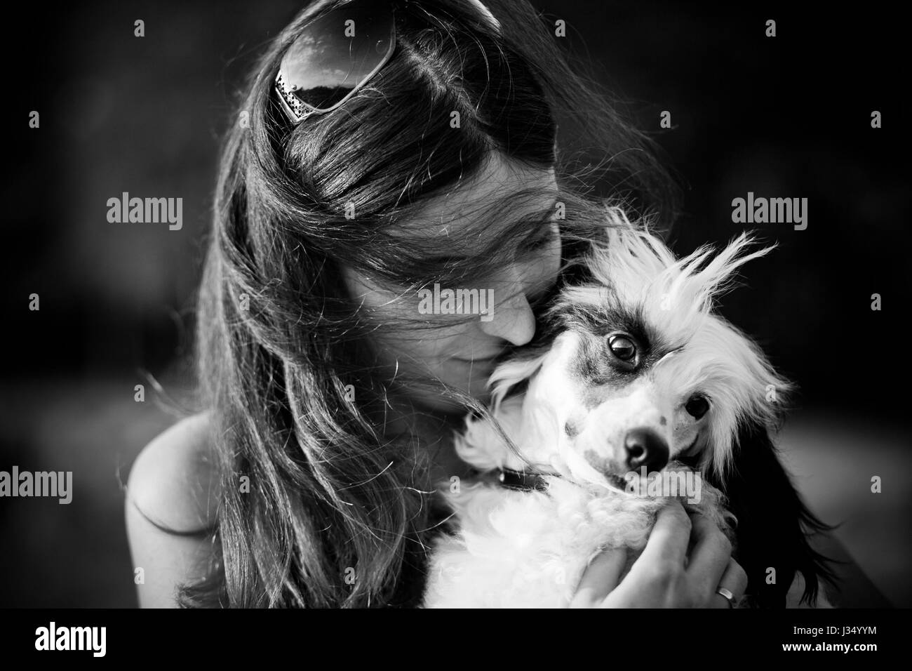 Beautiful young woman and her chinese crested dog outdoors. Monochrome. Grain added. - Stock Image