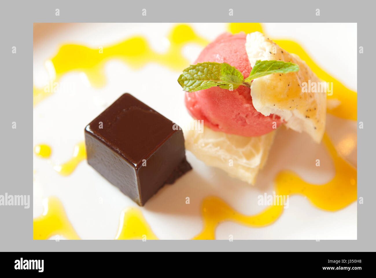 Overhead view of flourless chocolate torte with puff pastry and strawberry ice cream on a white plate Stock Photo