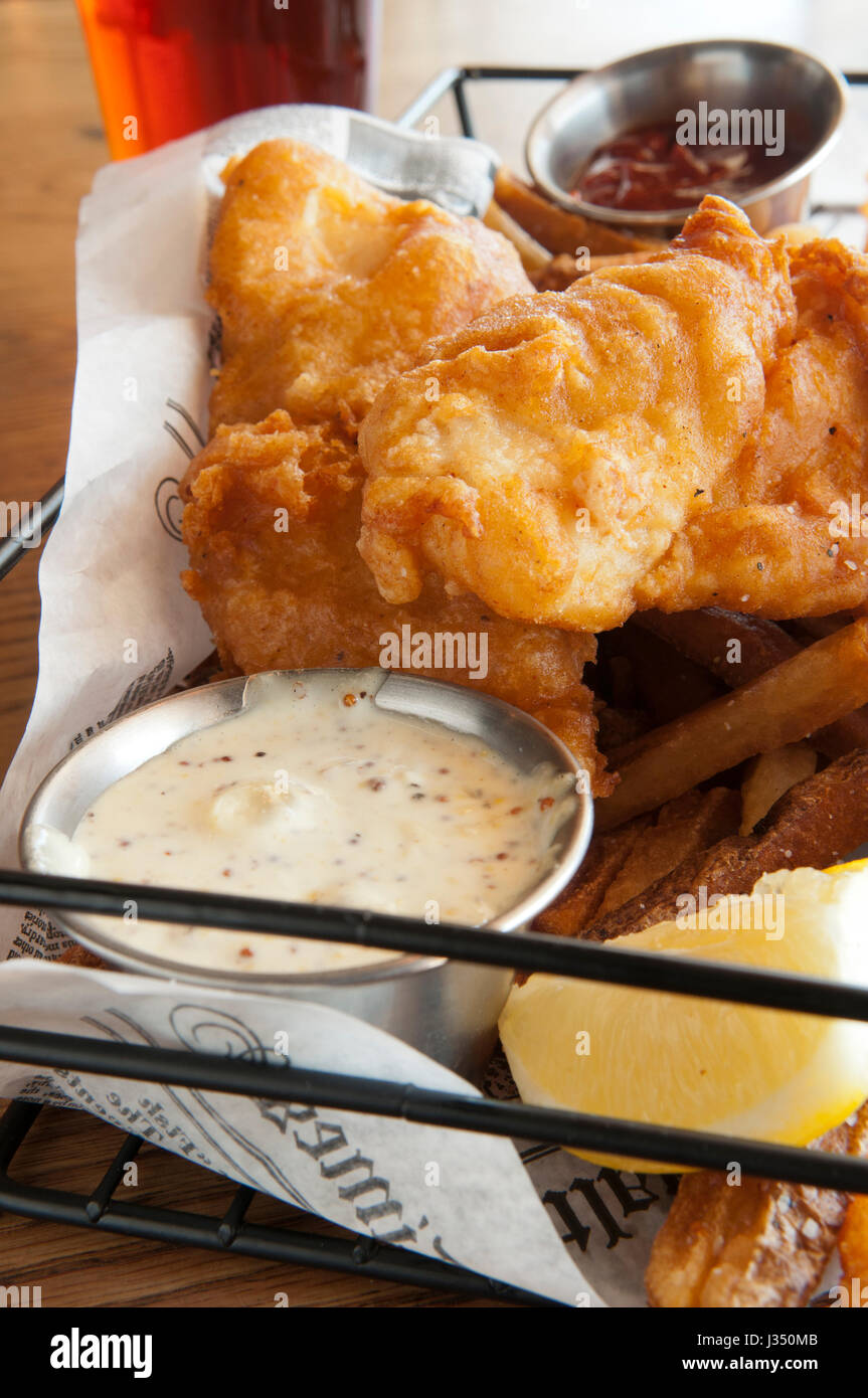 Close-up of a basket of fish and chips, or french fries, served with tartar sauce, catsup, and a cold beer - Stock Image
