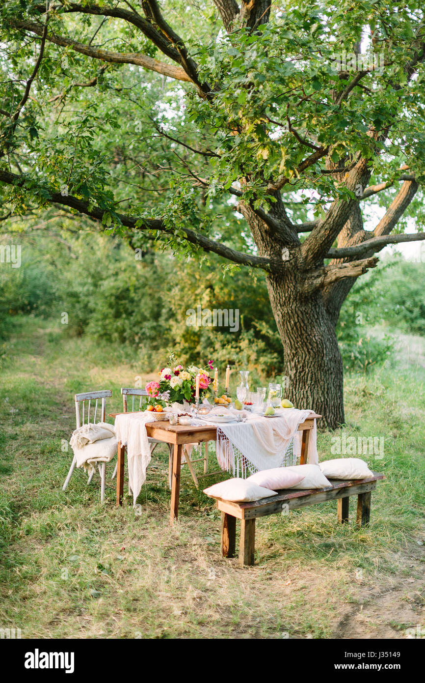 picnic summer holiday concept - festive table setting under big oak tree in forest openwork white tablecloth wooden bench and chairs colorful bouquet ... & picnic summer holiday concept - festive table setting under big ...