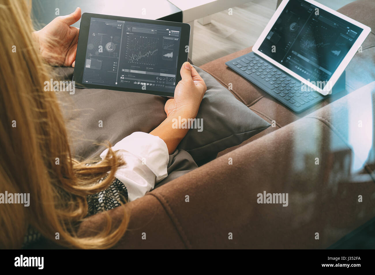 brunette woman using digital talet and laptop computer on sofa in living room - Stock Image