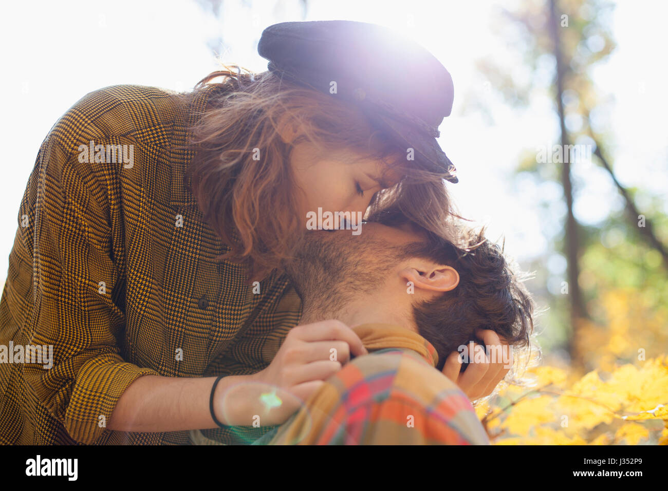 Happy young couple kissing in a park - Stock Image