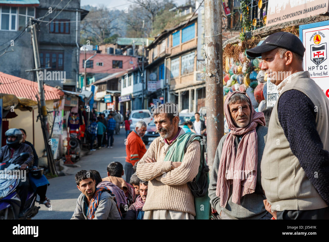 Indian lifestyle: local men standing around waiting patiently in a crowded street in McLeodGanj, Dharamshala, Himachal - Stock Image
