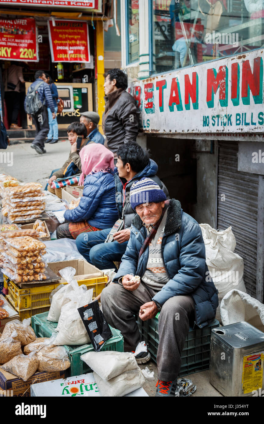 Local street seller, an old man of Tibetan ethnicity, sitting eating at a roadside stall in McLeodGanj, Dharamshala, - Stock Image