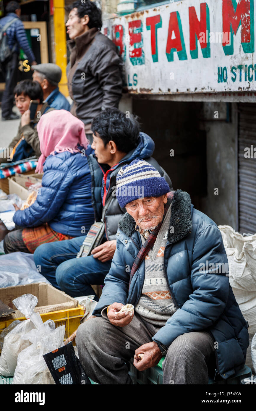Local old man of Tibetan ethnicity sitting eating on the roadside selling street food in McLeodGanj, Dharamshala, - Stock Image