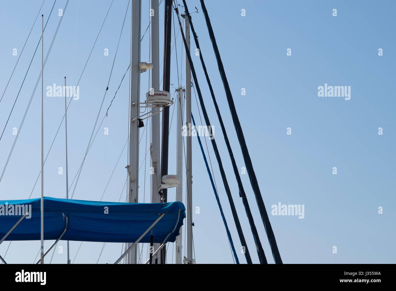 The masts of parked sailboats make patterns against the sky. - Stock Image