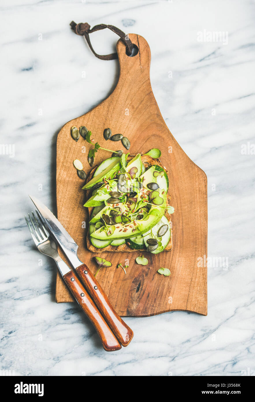 Healthy green veggie sandwich with avocado, cucumber, seeds, sporouts - Stock Image