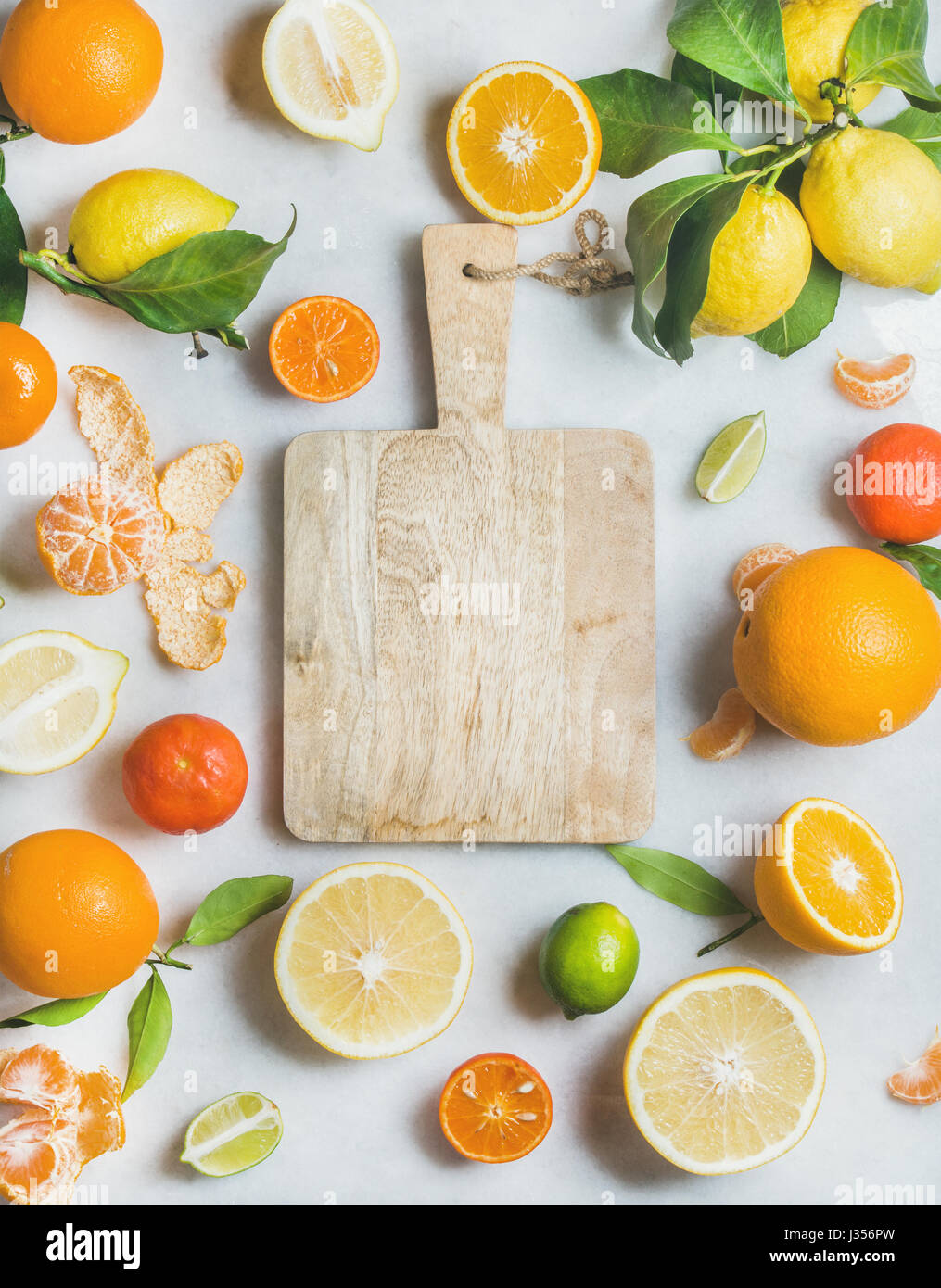 Variety of fresh citrus fruit and wooden board in center - Stock Image