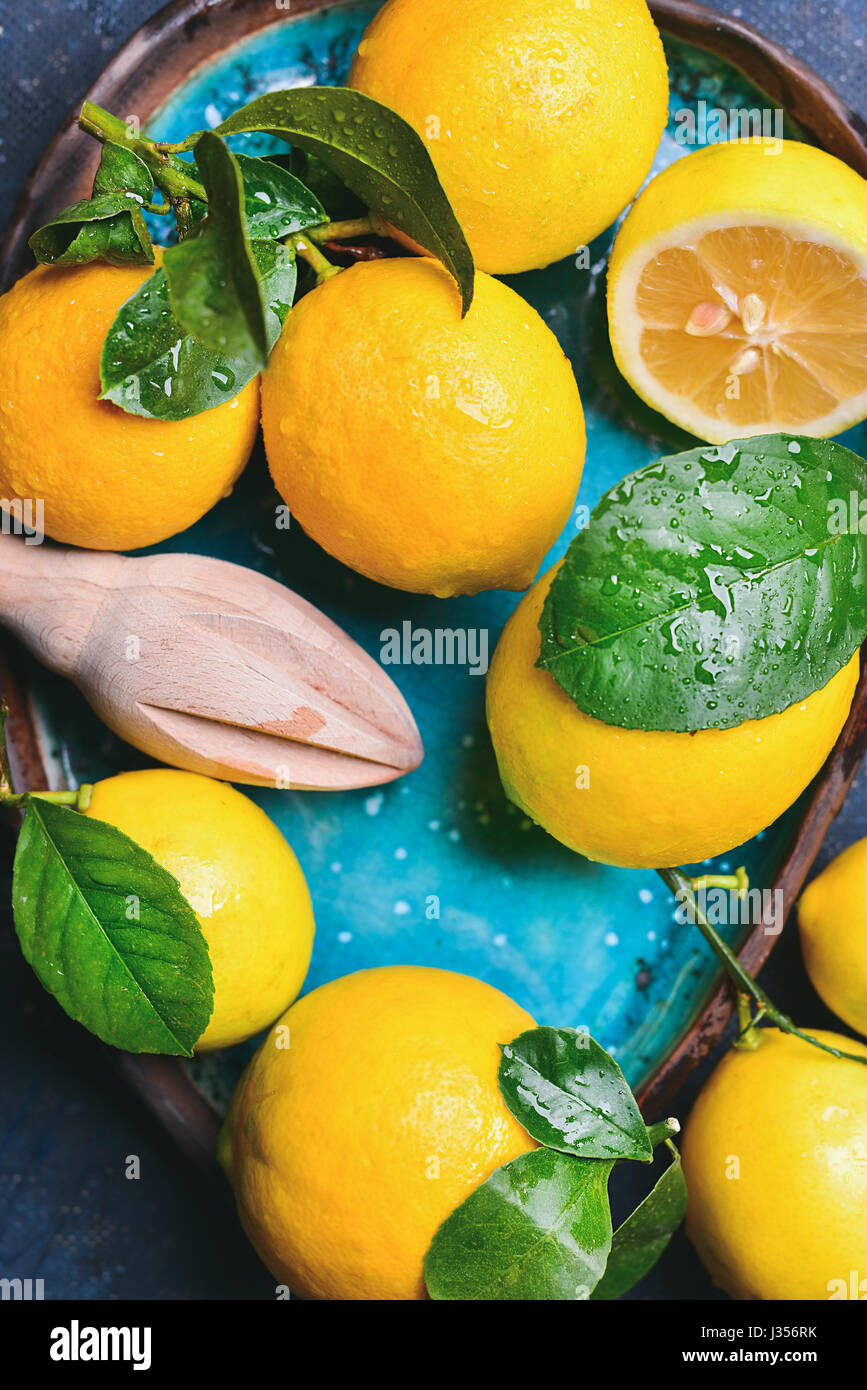 Close-up of freshly picked lemons with leaves in blue plate - Stock Image
