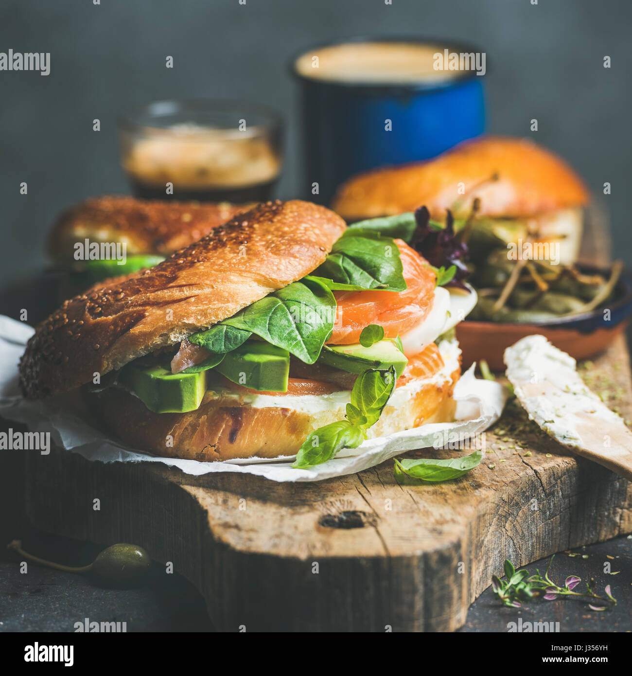 Close-up of bagel with salmon, cream-cheese, vebegables and coffee espresso - Stock Image