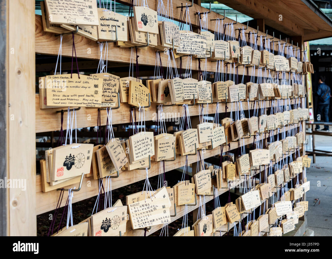 Ema, wooden plates with written prayers and wishes.Rows of wishing plaques at a shinto shrine. - Stock Image