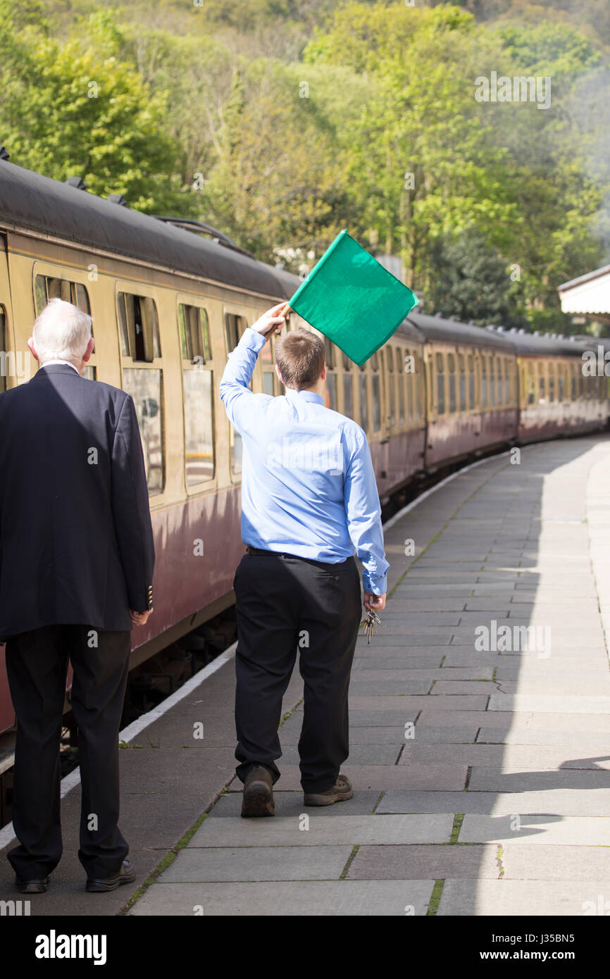 Llangollen steam train conductor waving flag to the driver to begin the train journey along in summer, Llangollen, - Stock Image