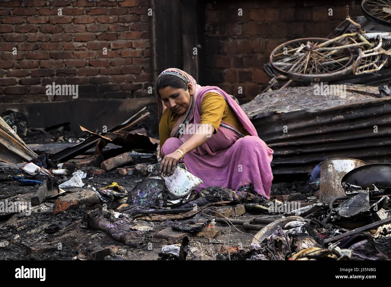 Guwahati, Assam, India. 3rd May, 2017. A woman pulling out half burnt text books of her children from the burnt - Stock Image