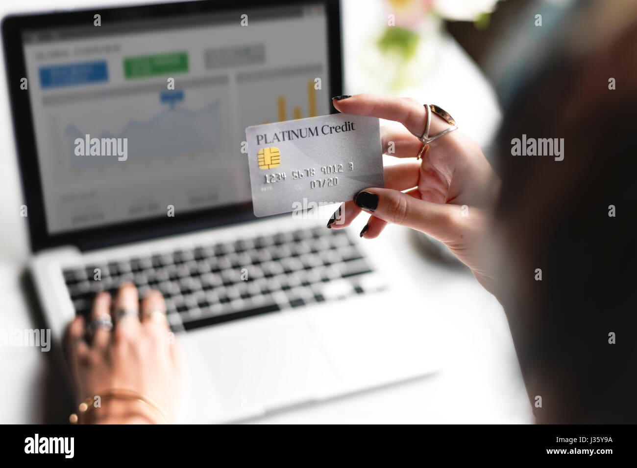 Woman Hand Holding Platinum Credit Card with Laptop Background - Stock Image