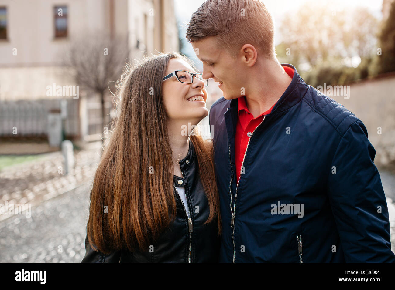 A young couple in love embracing and looking into each others eyes - Stock Image