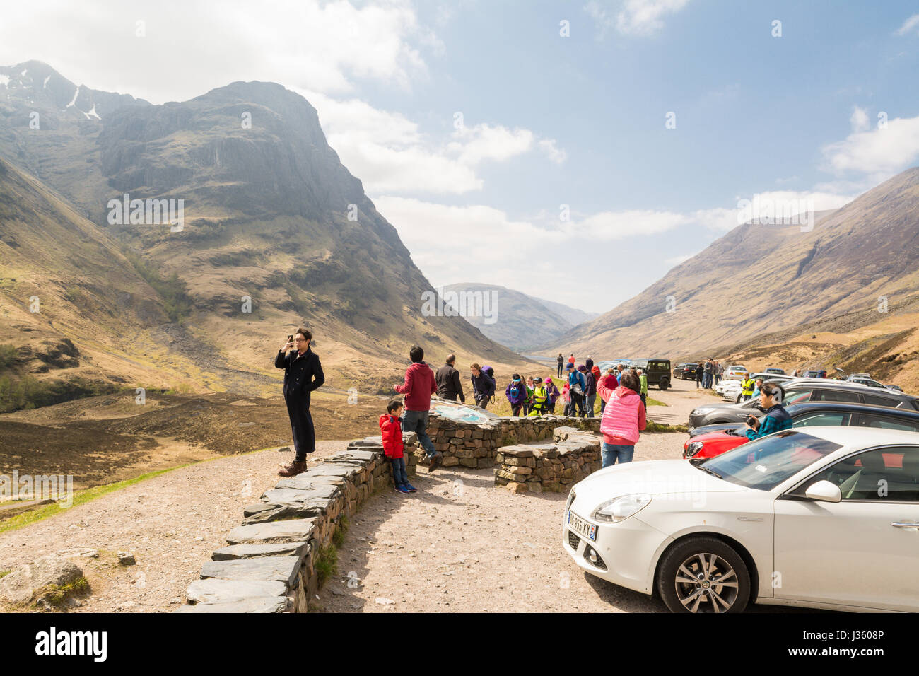 Glencoe, Scotland - tourists at the Three Sisters viewpoint, Scottish HIghlands - Stock Image