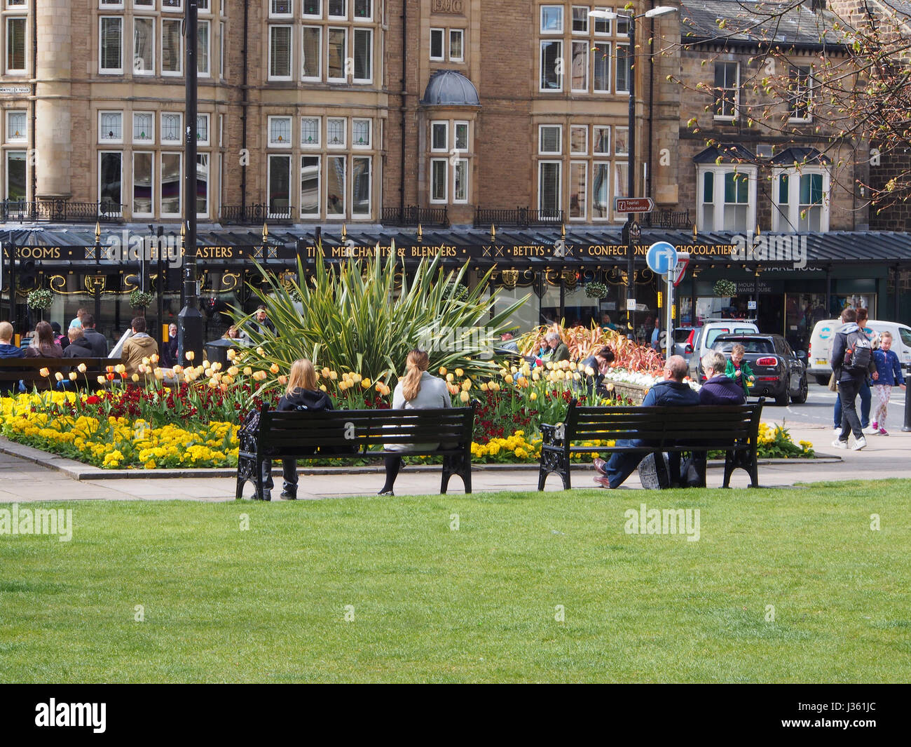 People relaxing in the sun in gardens in the centre of the Montpellier District of Harrogate, Yorkshire, UK, with - Stock Image