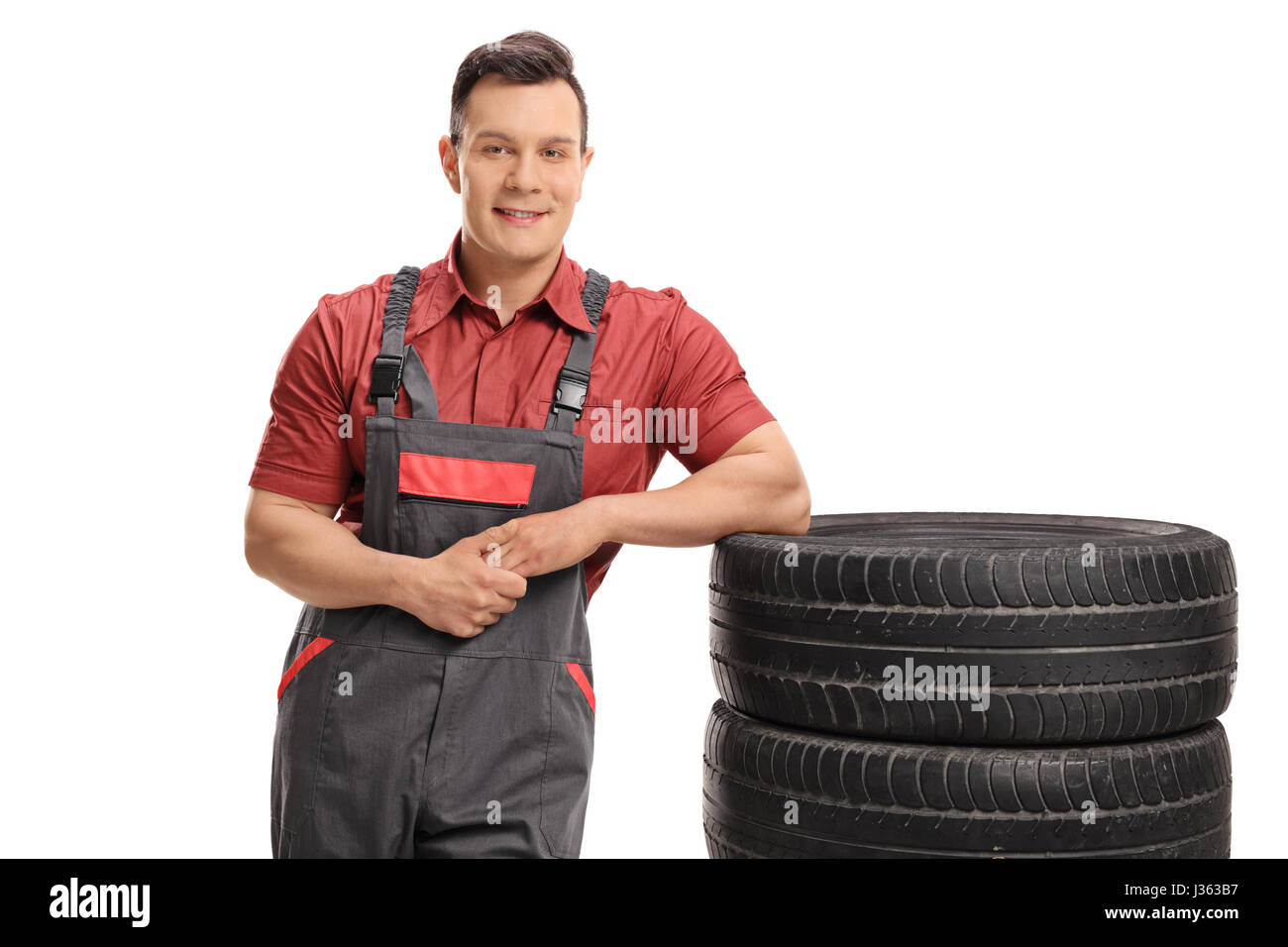 Mechanic leaning on a stack of tires and looking at the camera isolated on white background - Stock Image