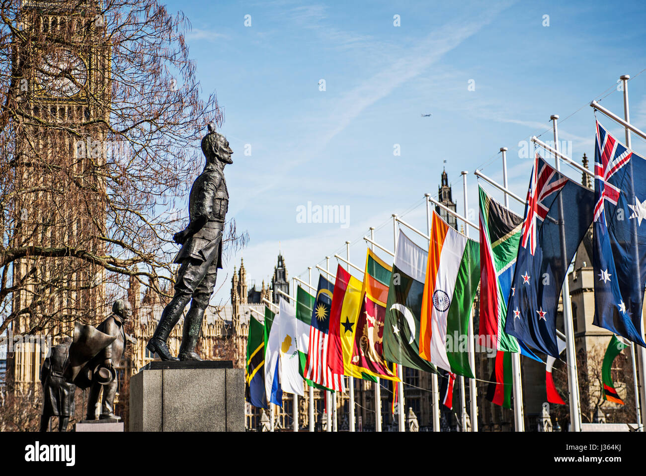 Statue of Jan Christian Smuts (1870 - 1950) outside parliament with flags and Big Ben. - Stock Image