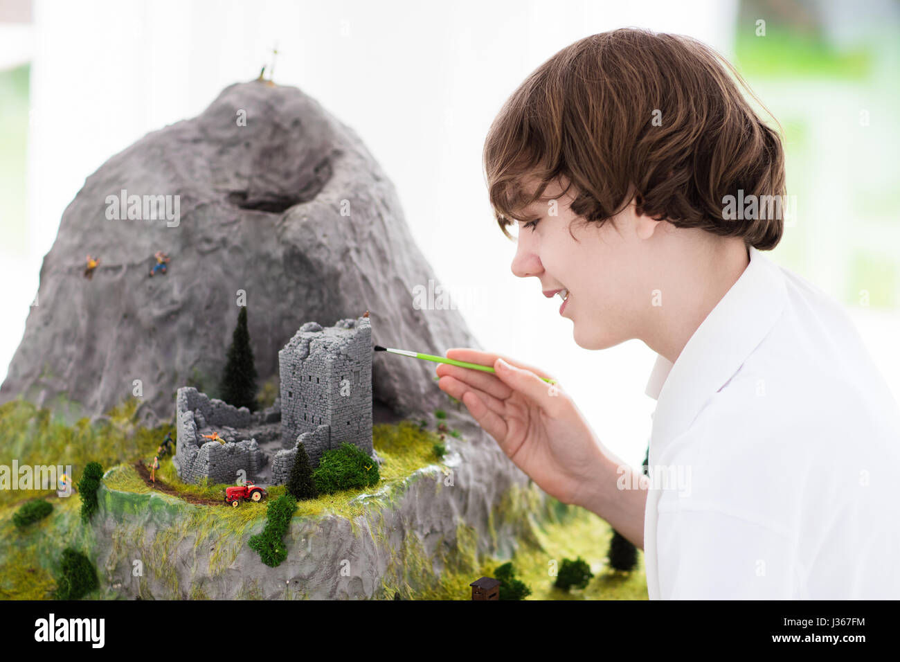 Teenager working on model building school project. Kids build miniature scale model mountain for geography class - Stock Image
