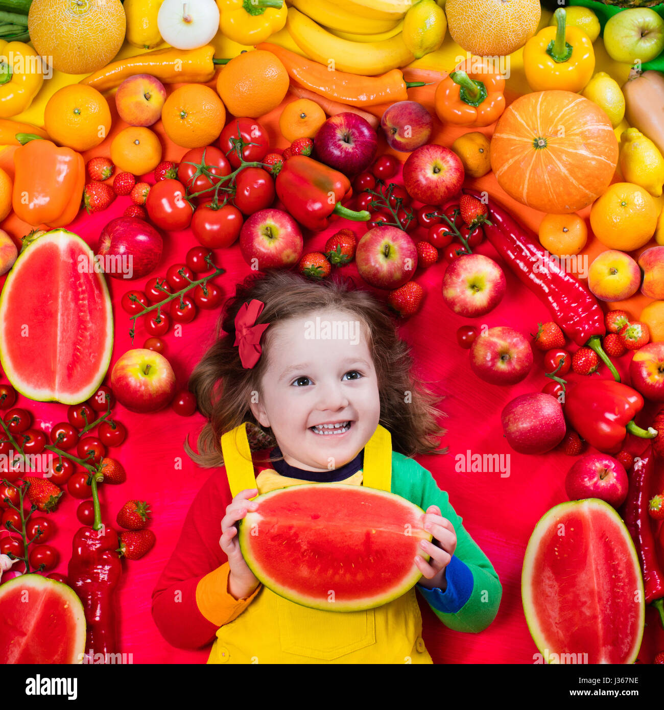 Little girl with variety of fruit and vegetable. Colorful rainbow of raw fresh fruits and vegetables. Child eating - Stock Image