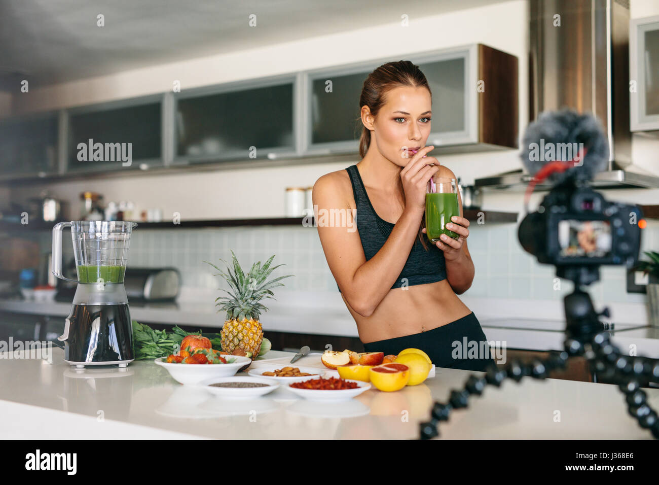 Young lady drinking green juice at the kitchen table looking at a camera mounted on tripod. Woman preparing a healthy - Stock Image