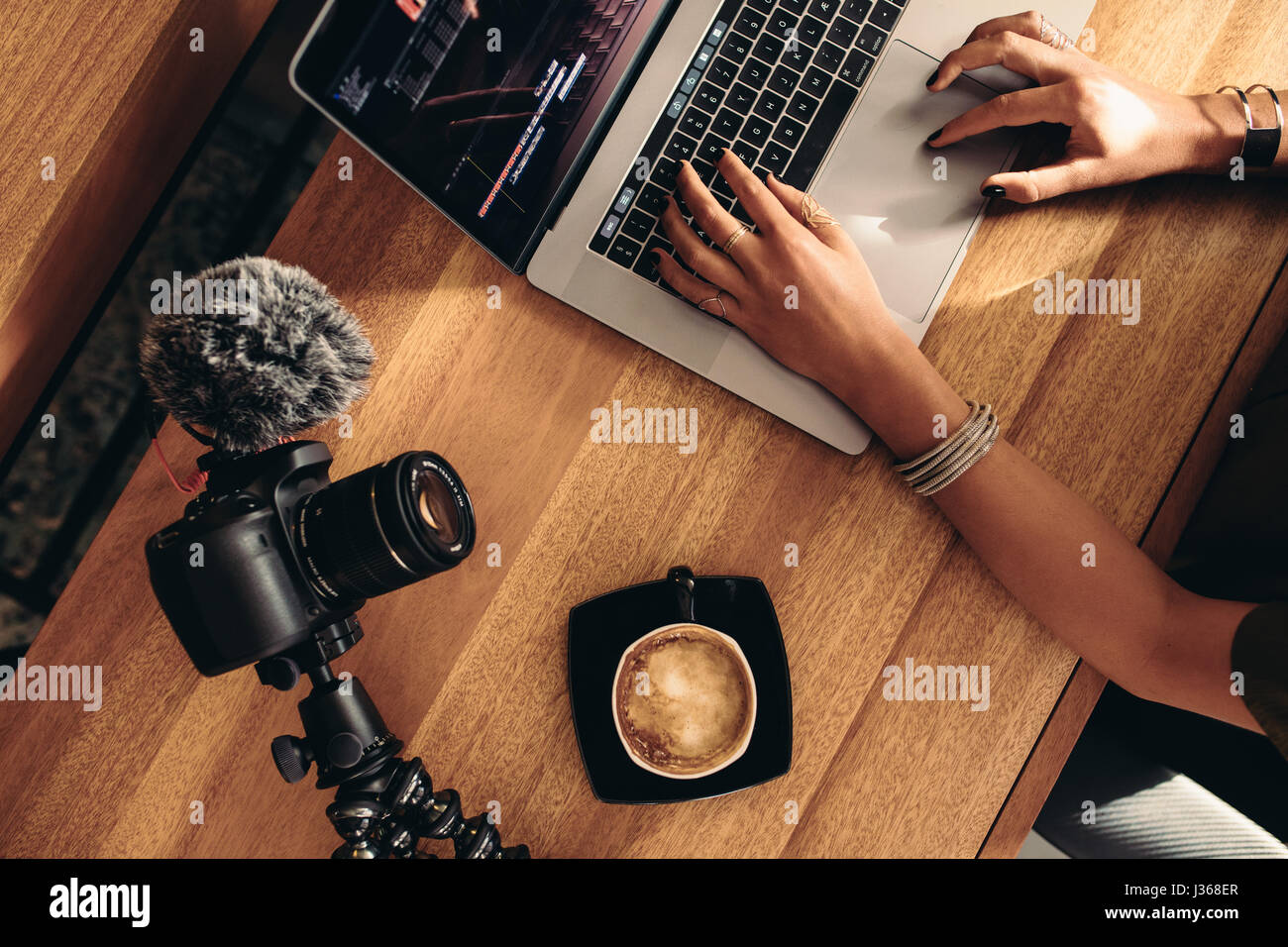 Top view of female vlogger editing video on laptop. Young woman working on computer with coffee and camera on table. - Stock Image