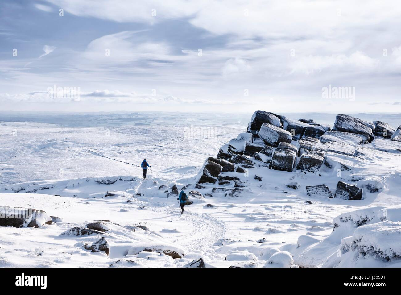 Hikers on Kinder Scout in winter snow, Peak District, UK - Stock Image