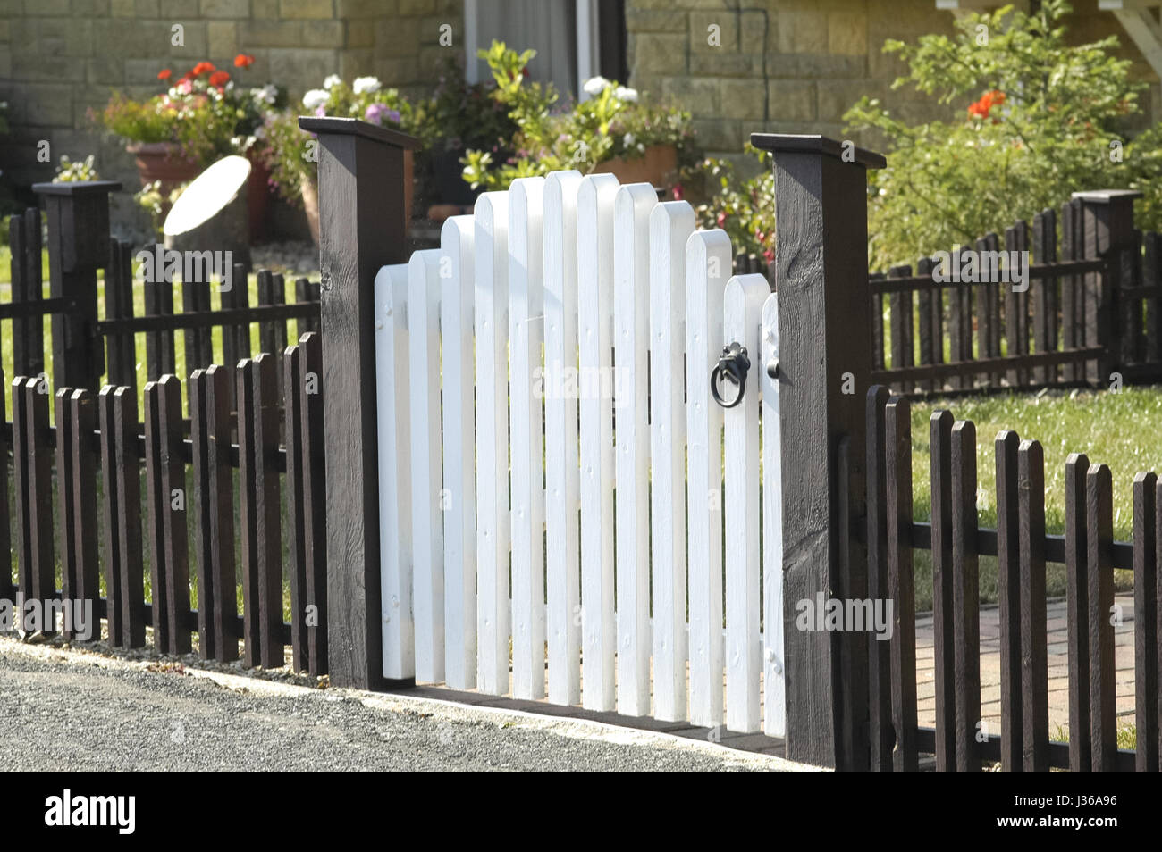 White Wooden Gate And Low Fence Around A Garden Stock