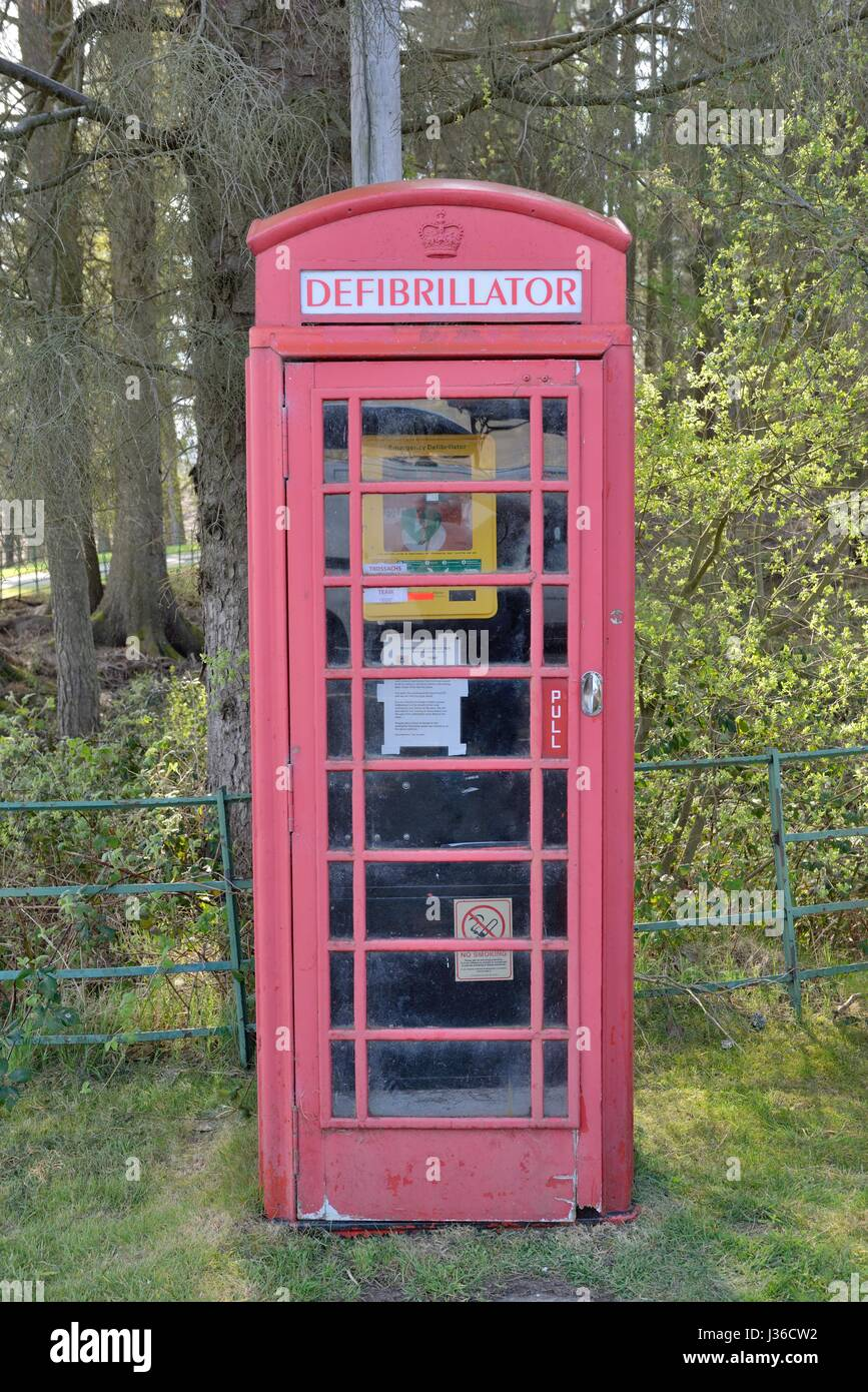 An old BT telephone box now housing an emergency defibrillator for public use in a remote location in Scotland, - Stock Image