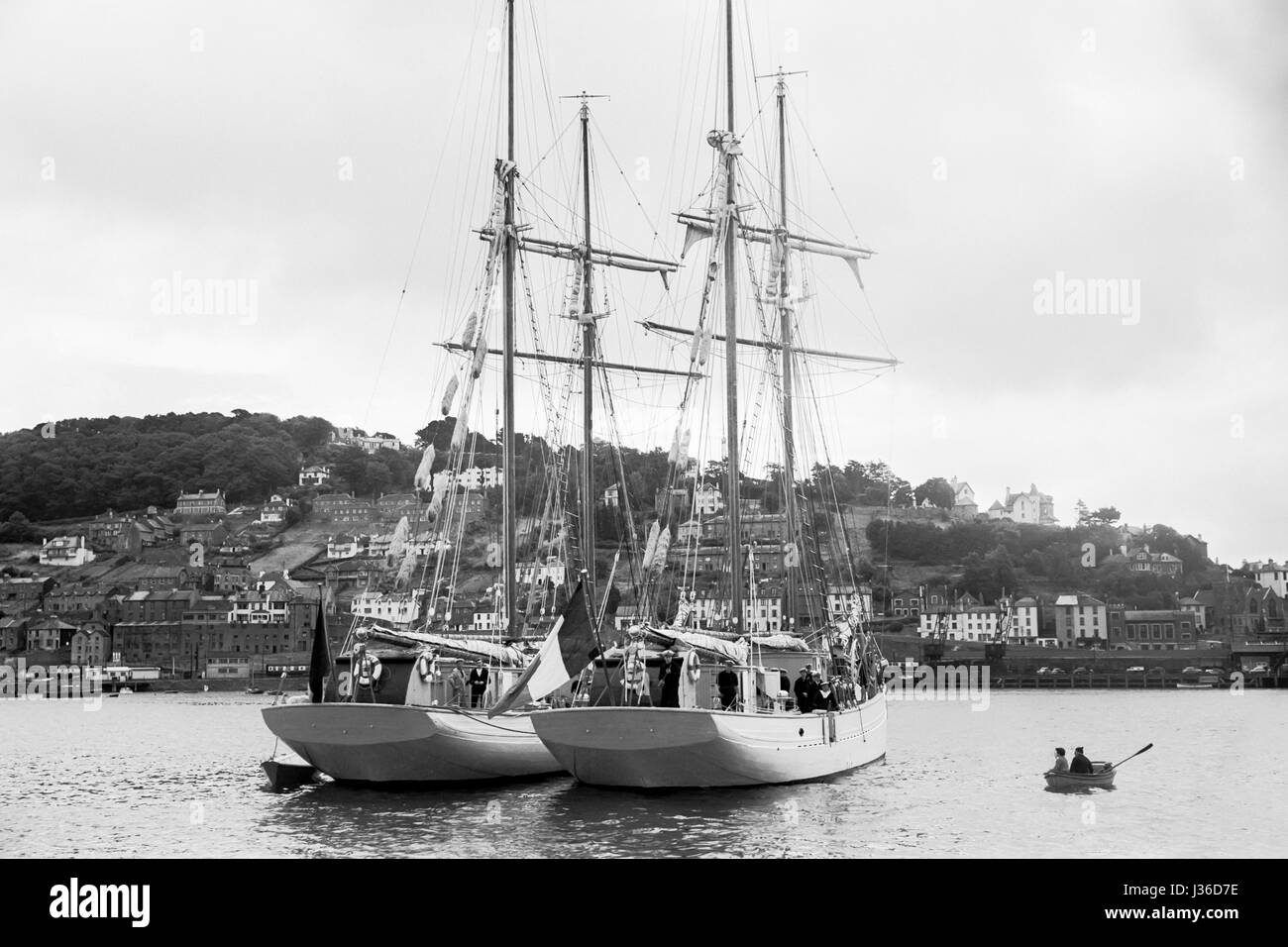 A small rowing boat approaches two large  yachts anchored off Torquay Devon. Circa 1920 - Stock Image