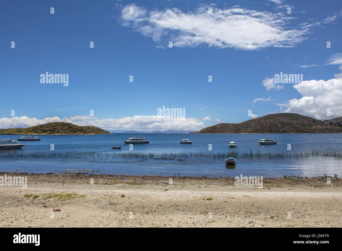 View with lake and boats. Road and boat trip to Isla del Sol, Island of the Sun. Located in Lake Titicaca in Bolivia. - Stock Image