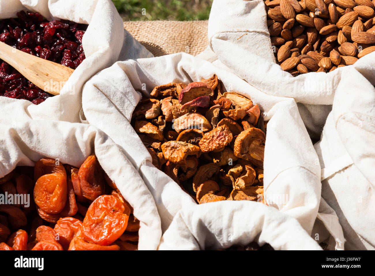 Dried apricots, apples, raisins and almond nuts in small white linen sacks on display for sale at local food fair. - Stock Image