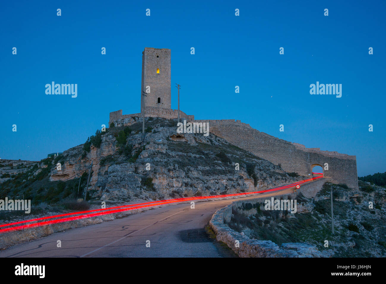 Ruins of medieval tower and red light trail, night view. Alarcon, Cuenca province, Castilla La Mancha, Spain. - Stock Image