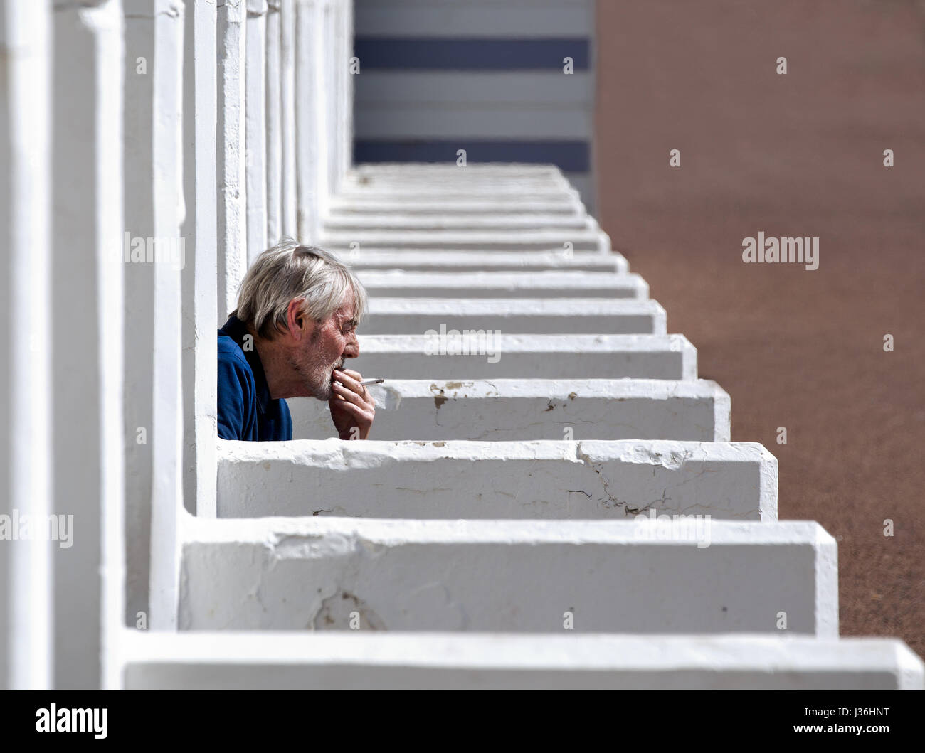 Head and shoulders of a middle-aged man sitting in a seafront cubicle whilst smoking a cigarette and thinking with - Stock Image