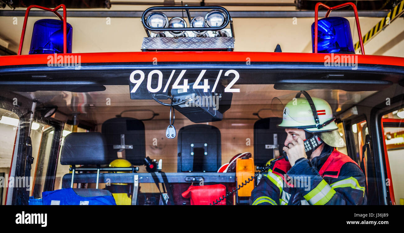 Firefighter in a fire truck in action with walkie talkie - HDR - Stock Image