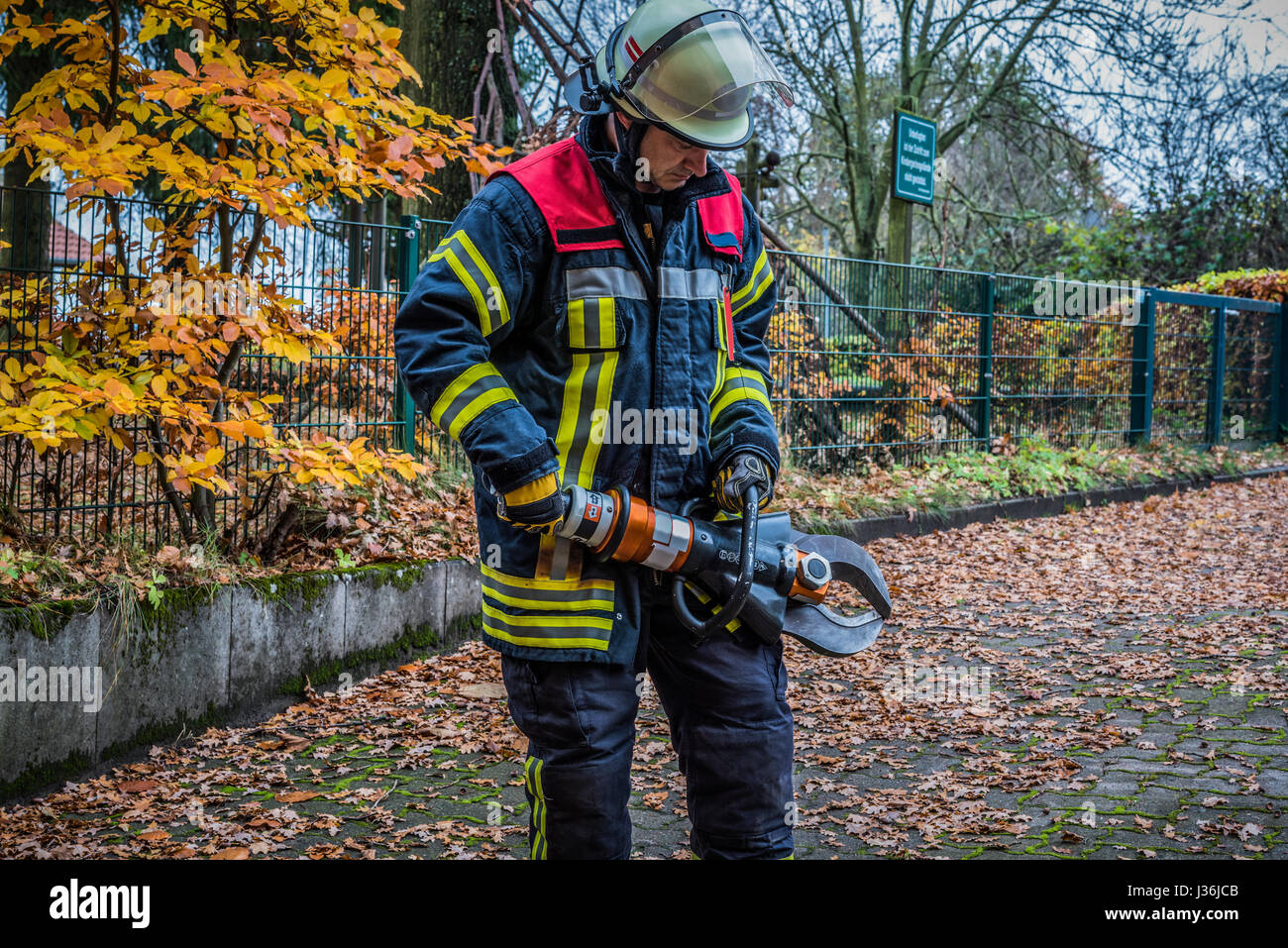 Firefighter in action with a  large forceps to open from car doors - HDR - Stock Image