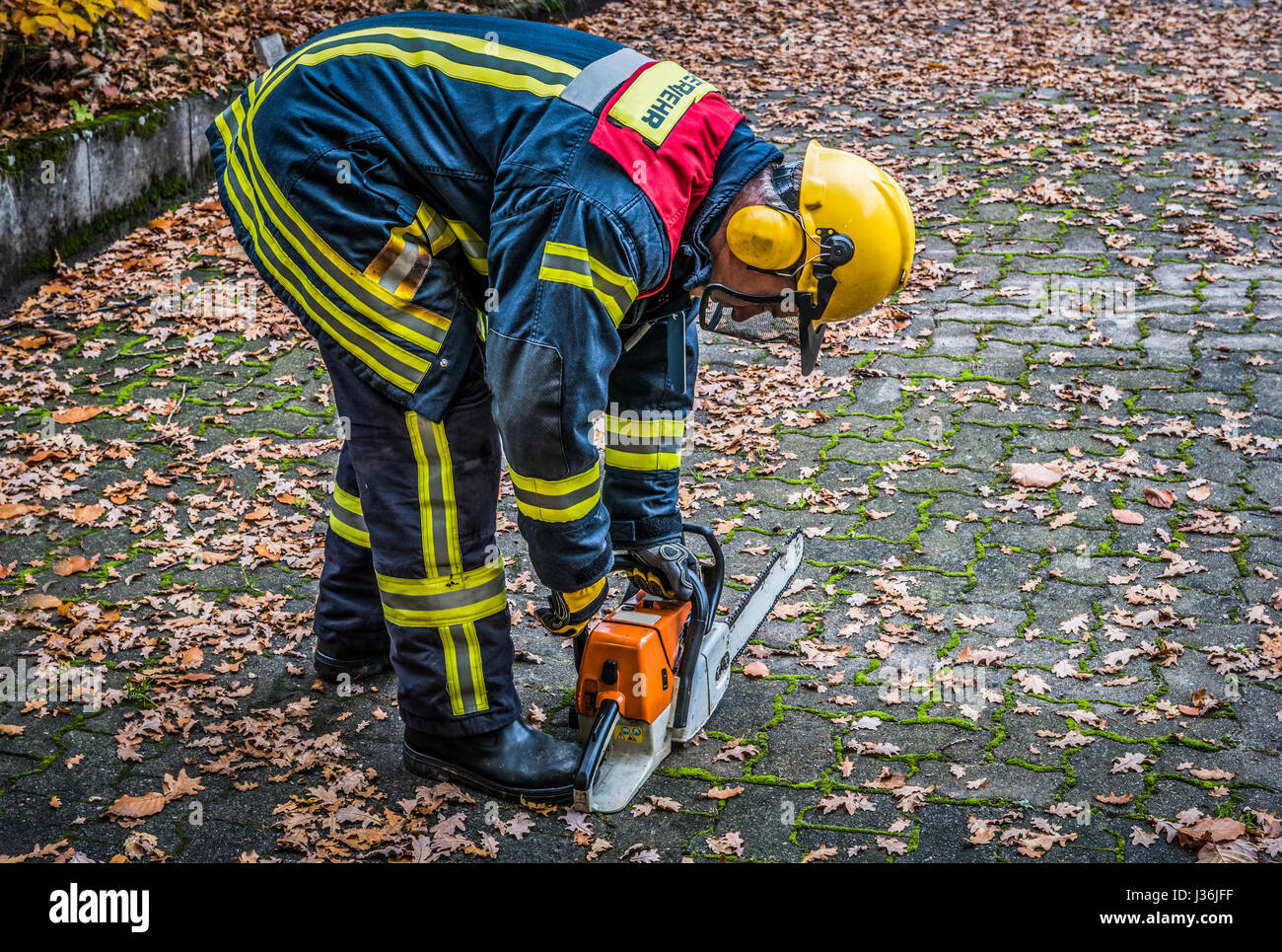 Firefighter in action with a chain saw - HDR - Stock Image