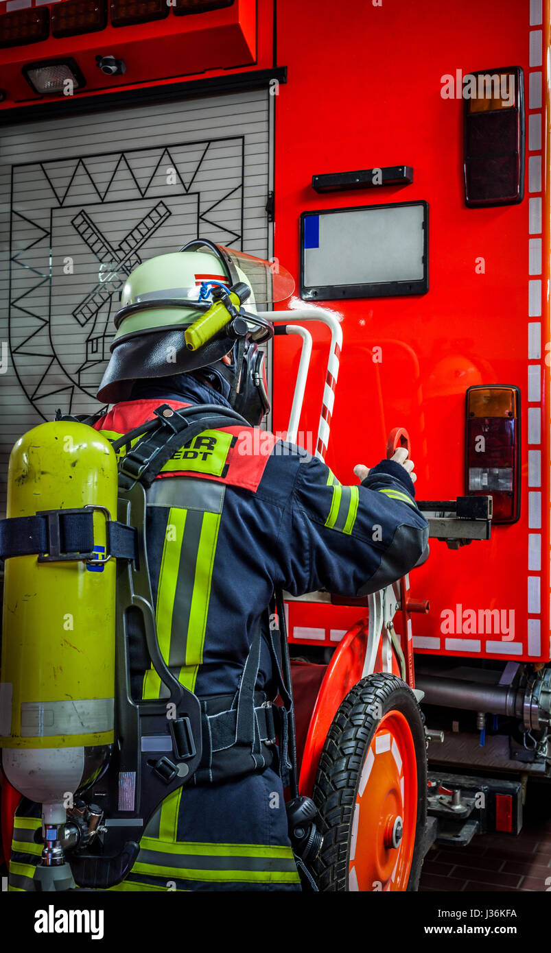 Firefighter in action on the emergency vehicle with oxygen bottle and respiratory protection mask - HDR - Stock Image