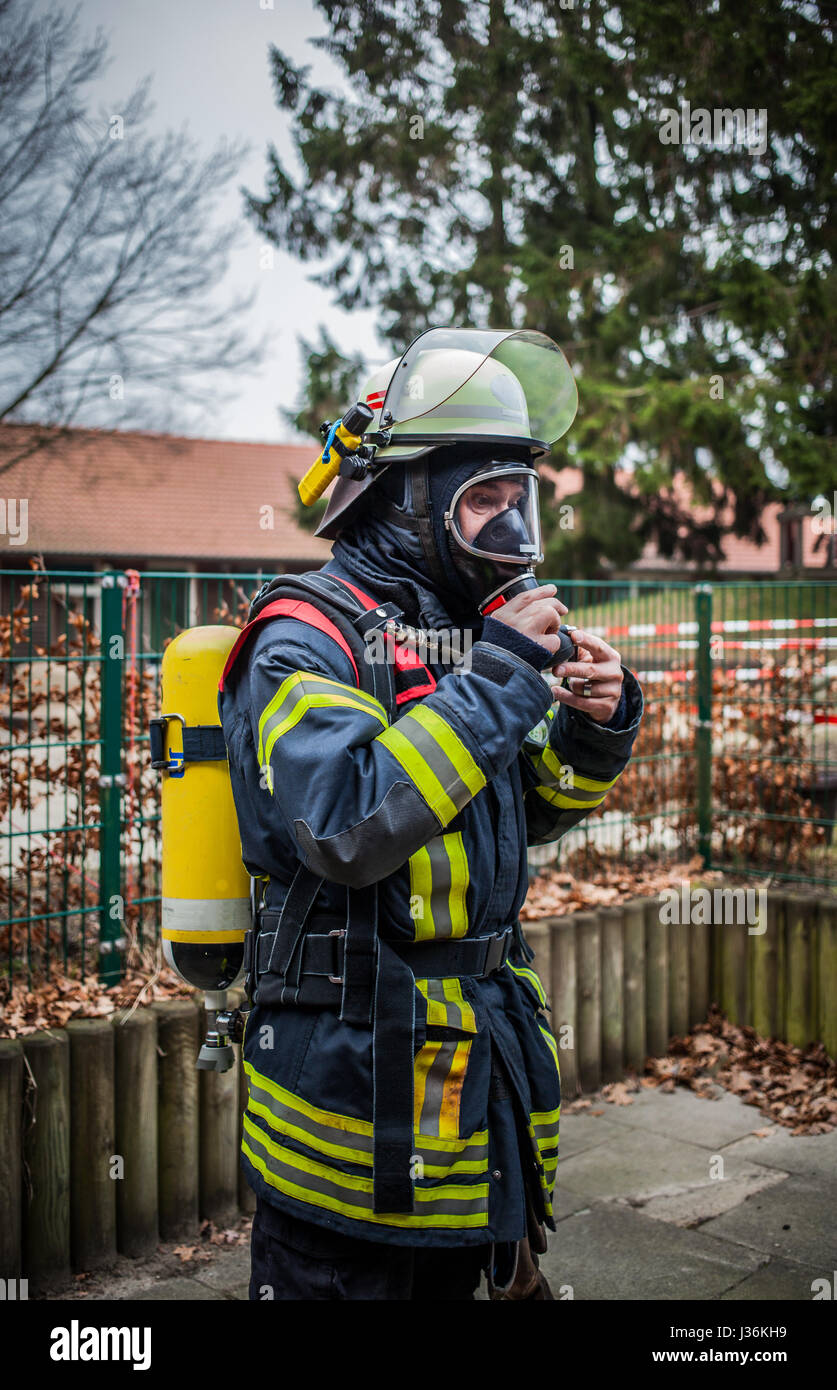 Firefighter outdoor in action with oxygen bottle and respiratory protection mask - HDR - Stock Image