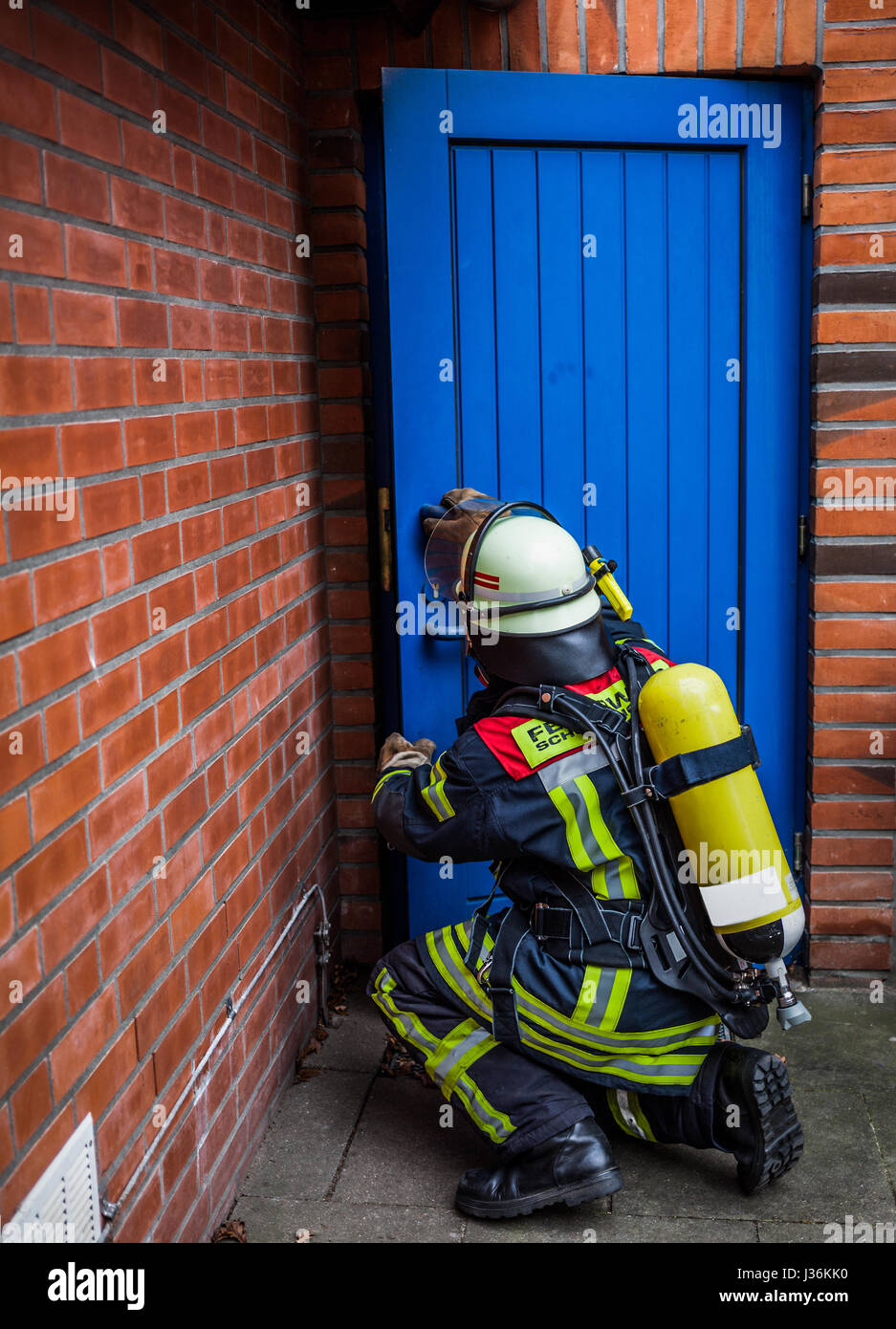 Firefighter opens a door in action with oxygen bottle and respiratory protection mask - HDR - Stock Image