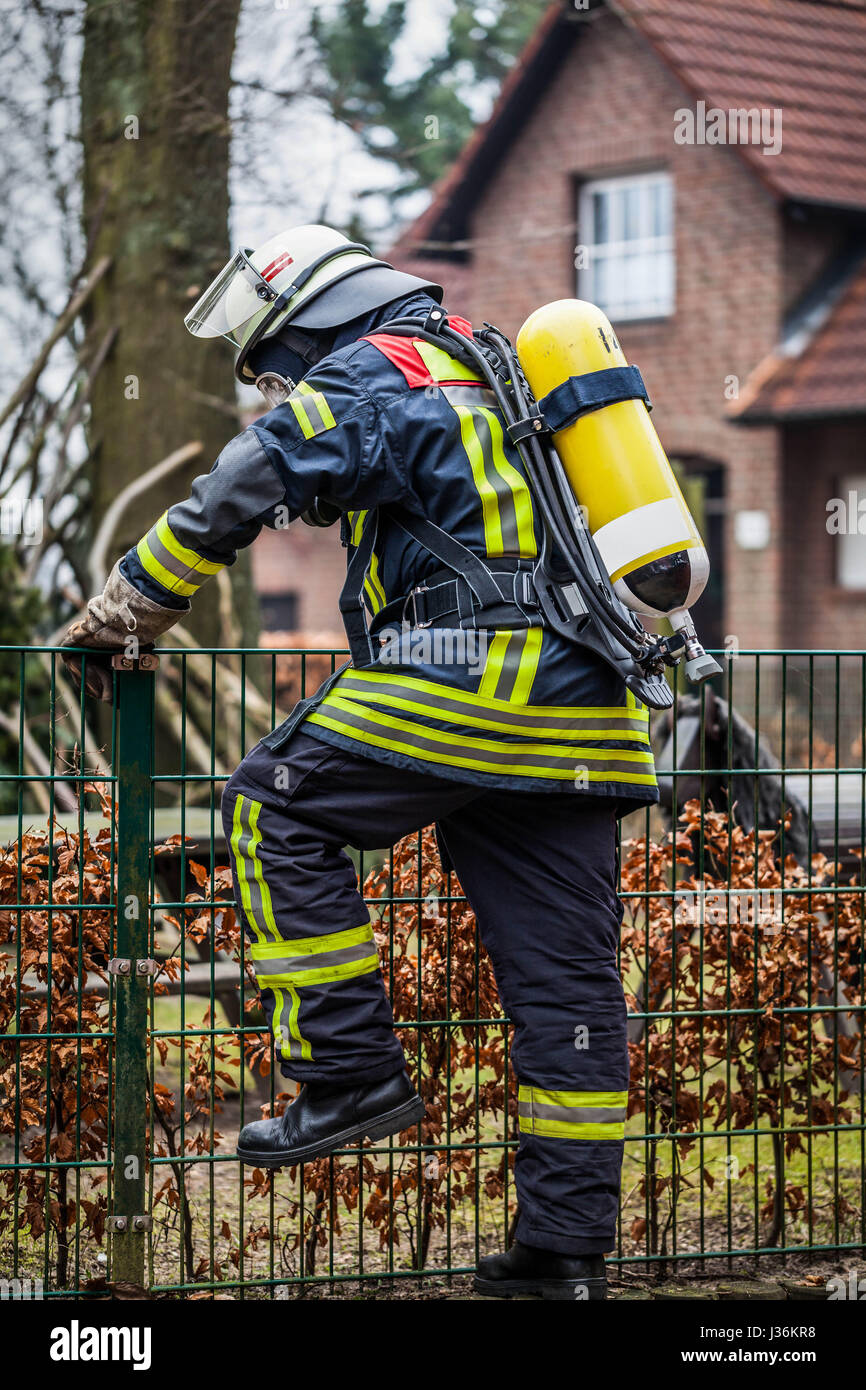 Firefighter in action outdoor with oxygen mask and oxygen cylinder - Stock Image