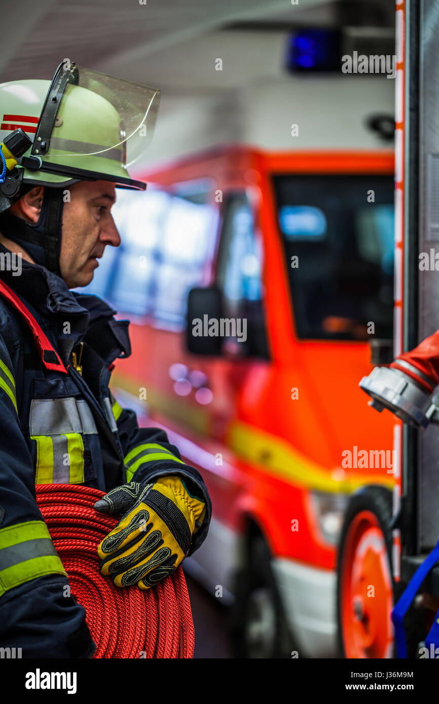 Firefighter in the fire station with a water hose in the hand - HDR - Stock Image