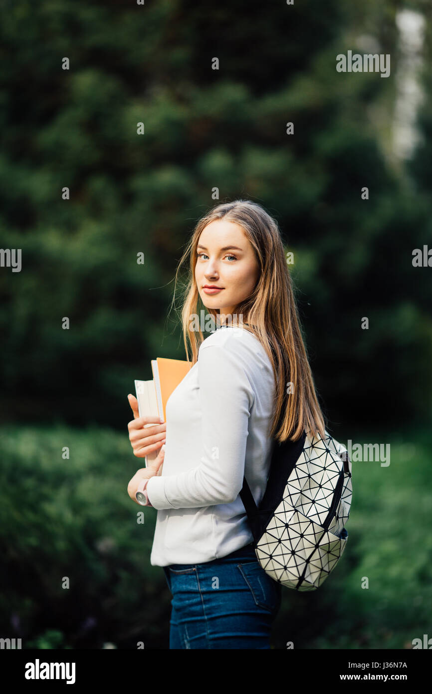 Outdoors portrait of a beautiful tanned teen student girl. - Stock Image