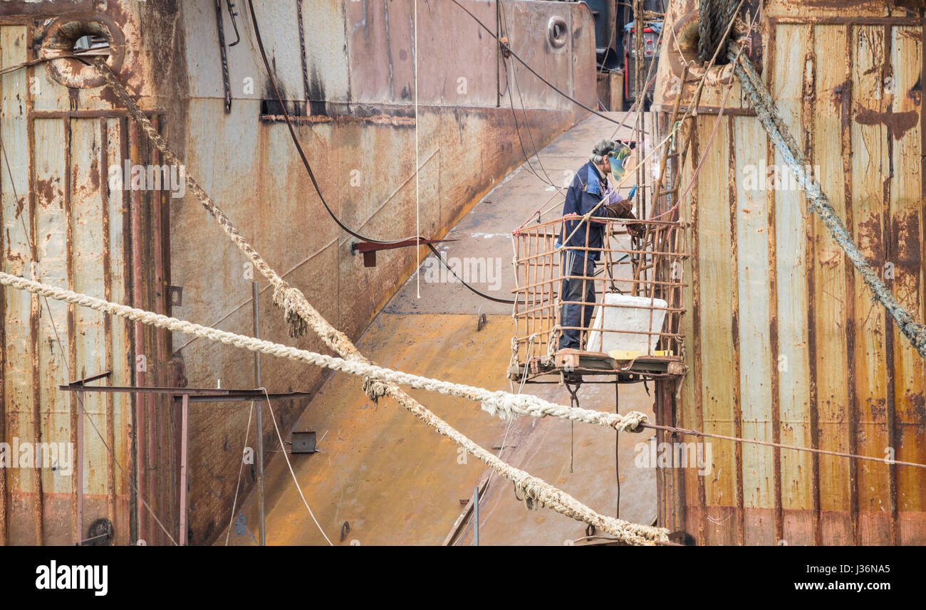 Crew repairing rusting Russian trawlers in port. - Stock Image