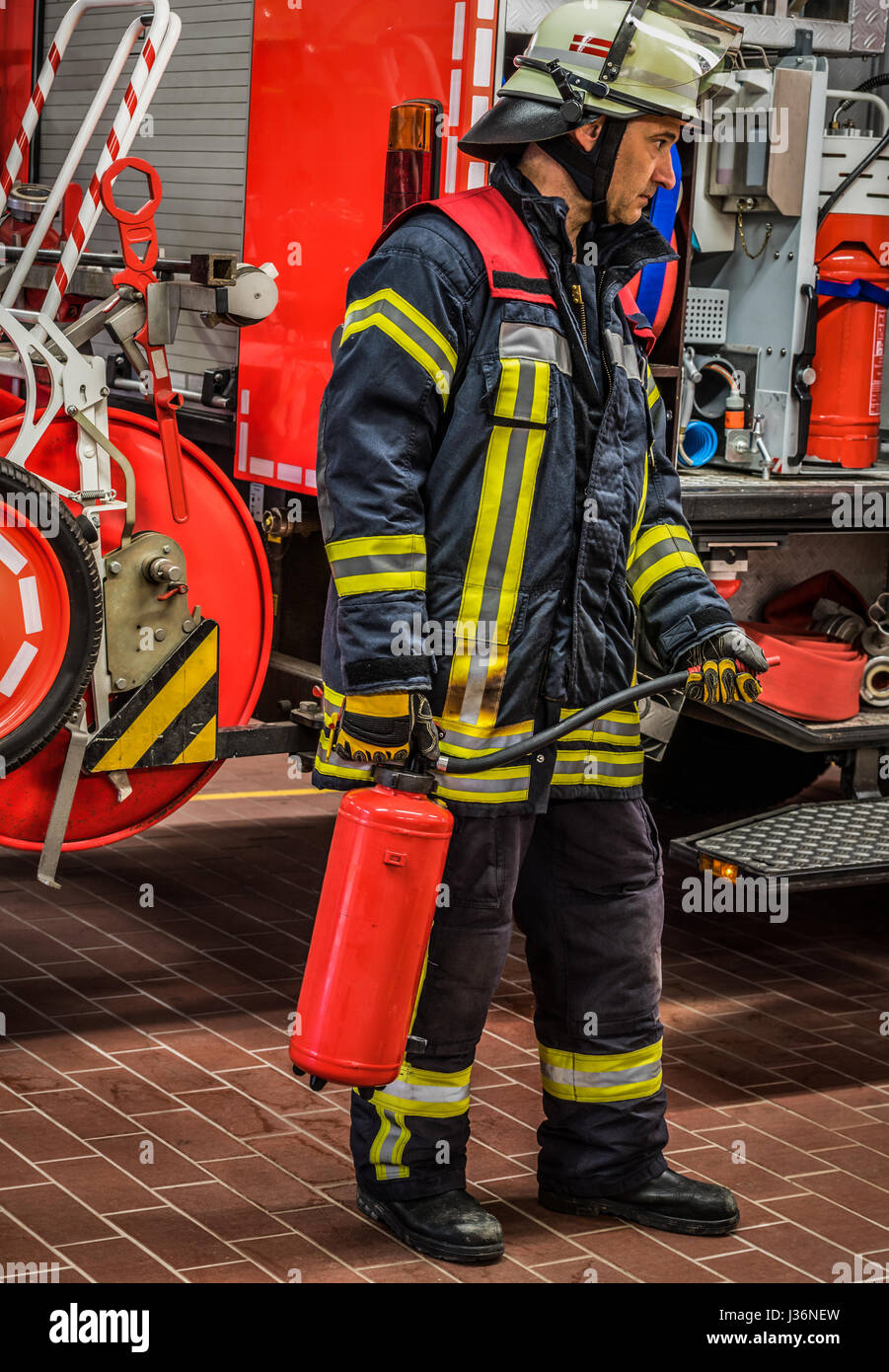 Firefighter in action with a professional extinguisher - HDR - Stock Image