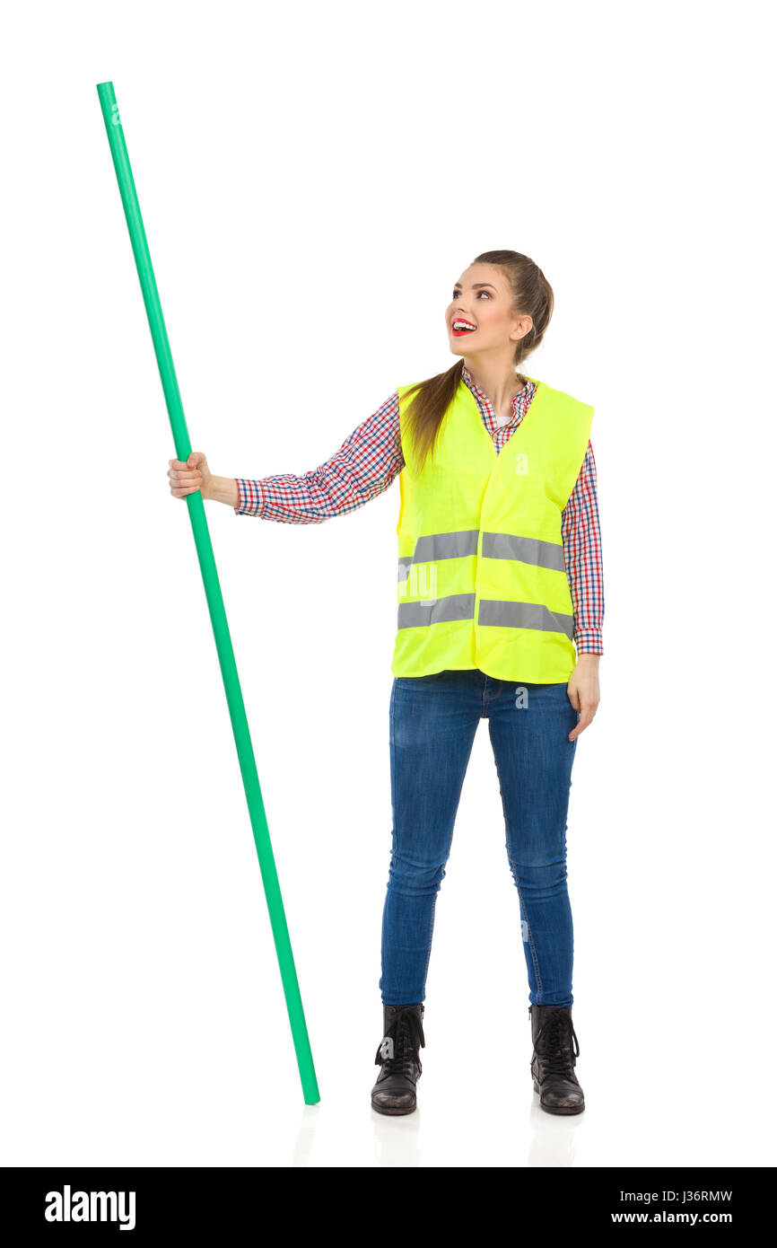 Young woman in yellow reflective vest, jeans, and lumberjack shirt standing legs apart, holding chroma key stick - Stock Image