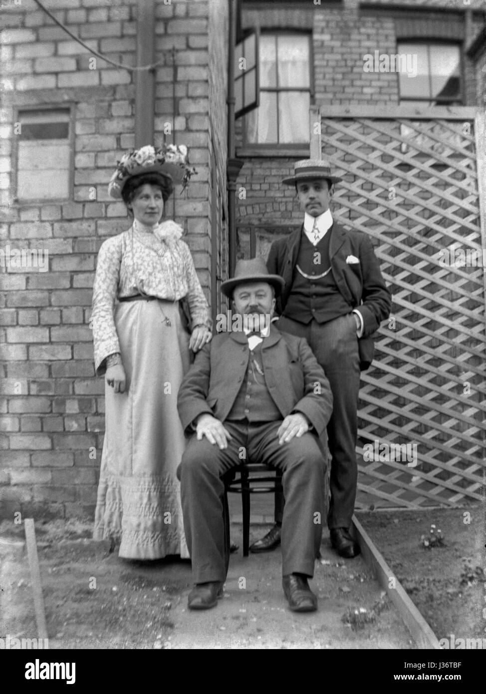 Edwardian family of three pose for a portrait in the backyard of a house in 1910. A bearded gentleman sits in a - Stock Image