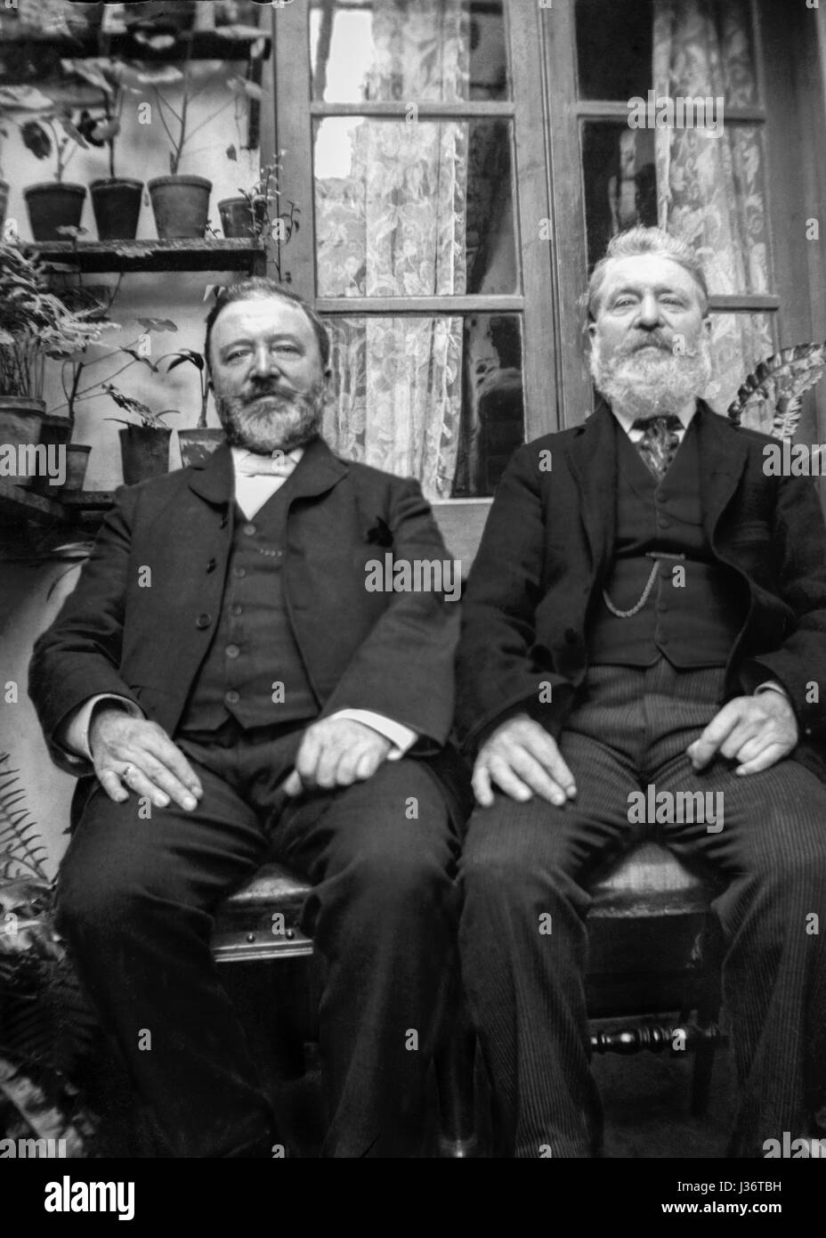Two bearded Edwardian gentlemen sat with hands on knees in small conservatory pose for a portrait. Photograph taken - Stock Image