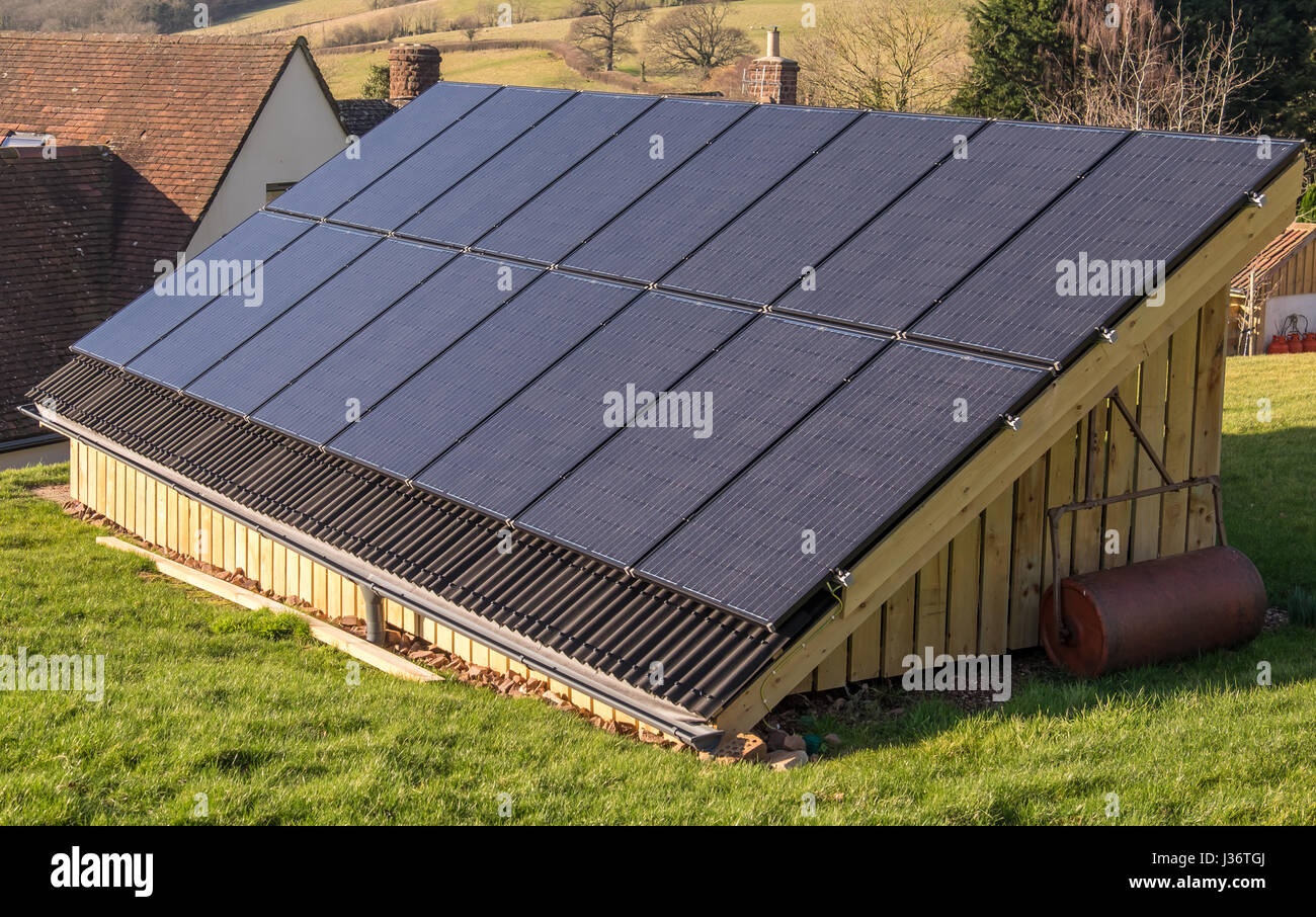 Photovoltaic Panels on the roof of an outbuilding at a house in a rural location in South West England - Stock Image